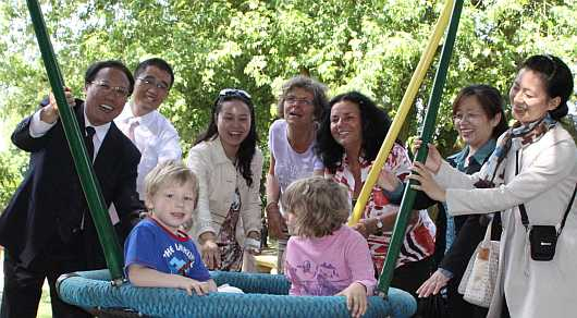 Chinesische Delegation mit Prof. Dr. renate Zimmer und der Kita-Leiterin vor Nestschaukel mit Kindern