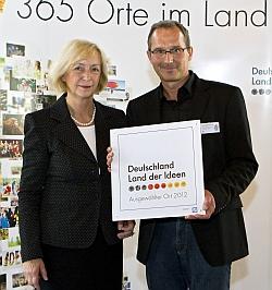 Ministerin Wanka überreicht nifbe-Vertreter Dr. Karsten Herrmann die Ehrentafel